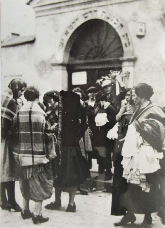 """תצלום מקורי מגטו בראשוב בקרקוב, נשים יהודיות על רקע בית הכנסת הרמ""""א (1943)."""